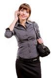 La mujer sonriente joven habla por un teléfono móvil Imagenes de archivo