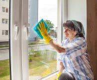 La mujer sonriente joven lava una ventana Imagen de archivo libre de regalías