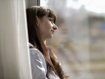 La mujer sonriente joven mira hacia fuera la ventana foto de archivo