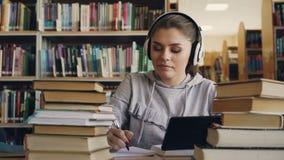La mujer sonriente joven positiva en los auriculares blancos se está sentando en la tabla en tableta digital de la biblioteconomí almacen de video