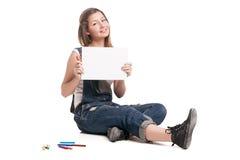 La mujer sonriente joven que se sienta en y la muestra Foto de archivo libre de regalías