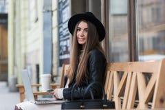 La mujer sonriente joven se vistió en teléfono de célula elegante de tenencia de la ropa mientras que se sentaba con el red-libro Imagenes de archivo