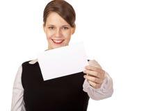La mujer sonriente joven sostiene la tarjeta de visita en cámara Fotos de archivo libres de regalías