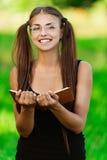 La mujer sonriente leyó el libro Fotos de archivo
