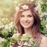 La mujer sonriente linda con las flores blancas enrruella al aire libre Fotos de archivo