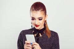 La mujer sonriente mira el teléfono emocionado encantado por el texto de mensaje que ella recibió imagen de archivo
