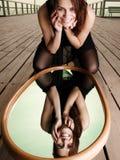 La mujer sonriente mira la reflexión en espejo Fotografía de archivo libre de regalías