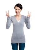La mujer sonriente muestra la muestra de la victoria con dos manos imagen de archivo