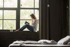 La mujer sonriente que disfruta del nuevo bestseller reserva sentarse en sil de la ventana Foto de archivo