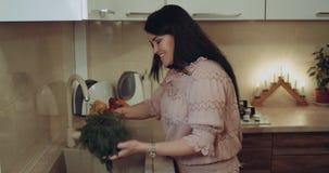 La mujer sonriente que lava en el fregadero las legumbres, fondo es la cocina blanca almacen de video