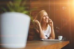 La mujer sonriente que llama con el teléfono móvil durante mañana desayuna en café Foto de archivo