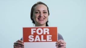 La mujer sonriente que lleva a cabo la muestra blanca sube para la venta almacen de metraje de vídeo