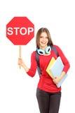 La mujer sonriente que lleva a cabo una señal de tráfico para y los cuadernos Imagen de archivo