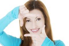 La mujer sonriente que lleva la blusa azul está mostrando el marco por las manos. Imagen de archivo