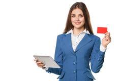 La mujer sonriente que muestra la tarjeta del crédito en blanco sostiene la PC de la tableta disponible, aislado sobre el fondo b Imagen de archivo