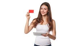 La mujer sonriente que muestra la tarjeta del crédito en blanco sostiene la PC de la tableta disponible, en la camiseta blanca, a Imagen de archivo
