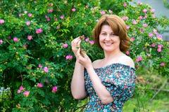 La mujer sonriente que se colocaba cerca de perro floreciente subió Imágenes de archivo libres de regalías