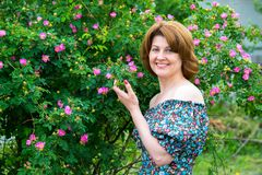 La mujer sonriente que se colocaba cerca de perro floreciente subió Fotografía de archivo