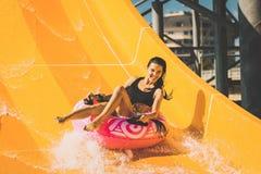 La mujer sonriente que se divierte en el tobogán acuático en aguamarina parquea fotos de archivo