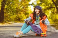 La mujer sonriente que se sienta en penique plástico del color sube Fotografía de archivo