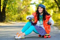 La mujer sonriente que se sienta en penique plástico del color sube Imagen de archivo libre de regalías