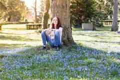 La mujer sonriente que se sienta en una primavera florece el prado Imágenes de archivo libres de regalías