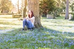 La mujer sonriente que se sienta en una primavera florece el prado Imagenes de archivo