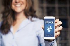 La mujer sonriente que sostiene un teléfono móvil con la huella dactilar desbloquea la notificación en la pantalla imagen de archivo