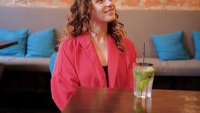 La mujer sonriente relajada del café del ocio sirvió el cóctel metrajes