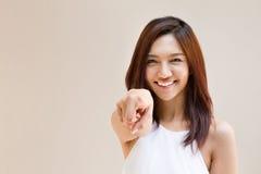 La mujer sonriente señala el finger en usted, humor positivo Fotos de archivo