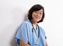 La mujer sonriente se cuida o la enfermera en azul friega Imagenes de archivo