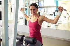 La mujer sonriente se está resolviendo en la máquina del tirón-abajo en gimnasio cerca del MI Imagen de archivo libre de regalías