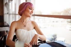 La mujer sonriente se está sentando en café-barra cómoda durante su tiempo de la reconstrucción imagen de archivo libre de regalías