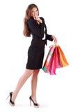 La mujer sonriente sostiene bolsos con las compras Foto de archivo libre de regalías