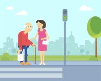 La mujer sonriente toma cuidado del viejo hombre para ayudarle a cruzar el camino Fotografía de archivo libre de regalías