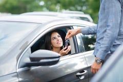 La mujer sonriente toma llave del coche Una mano del ` s del hombre da llaves del coche con los botones para abrir o para cerrar  Imagen de archivo libre de regalías