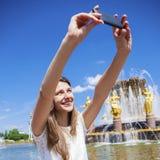La mujer sonriente toma una imagen de sí misma con un smartphone Selfi Imagen de archivo