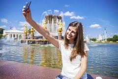 La mujer sonriente toma una imagen de sí misma con un smartphone Selfi Imagen de archivo libre de regalías