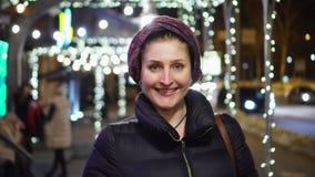 La mujer sonriente va en la cámara en un gorodk de la noche por la luz de bulbos brillantes almacen de video