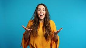 La mujer sorprendente feliz que dice sí y disfruta buenas noticias en fondo azul almacen de metraje de vídeo