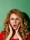 La mujer sorprendida grita las mejillas de los controles a mano en vidrios claros Expresiones faciales expresivas foto de archivo libre de regalías