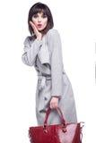 La mujer sorprendida se vistió en una capa gris y sostener un bolso rojo Foto de archivo libre de regalías