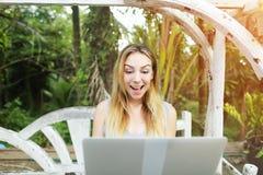 La mujer sorprendida utiliza el ordenador portátil que hace el trabajo en línea el día soleado, fondo de las palmas del verde de  Fotos de archivo