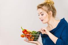 La mujer sostiene la cesta de compras con las verduras Imagenes de archivo