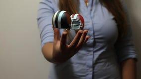 La mujer sostiene dos cascos de fútbol americano almacen de metraje de vídeo