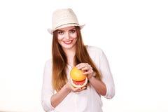 La mujer sostiene dos halfs de agrios del pomelo en manos Fotos de archivo