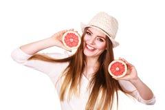 La mujer sostiene dos halfs de agrios del pomelo en manos Imagen de archivo libre de regalías