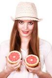 La mujer sostiene dos halfs de agrios del pomelo en manos Imágenes de archivo libres de regalías
