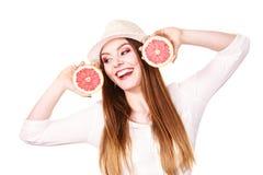 La mujer sostiene dos halfs de agrios del pomelo en manos Fotografía de archivo