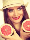 La mujer sostiene dos halfs de agrios del pomelo en manos Fotos de archivo libres de regalías